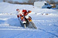 Équitation de Santa Claus sur une moto tournant le MX Photographie stock libre de droits