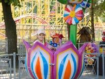 Équitation de six ans de fille sur un carrousel, séance dans le fleuron stylisé Photo libre de droits