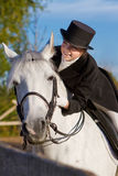 Équitation de sourire de femme sur un cheval blanc Photo stock