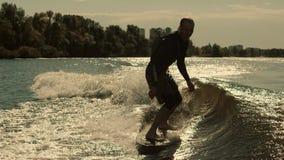 Équitation de sportif sur le ressac de sillage au coucher du soleil Formation folâtre d'homme sur le panneau de ressac banque de vidéos