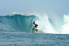 Équitation de surfer dans le baril sur l'onde parfaite image libre de droits