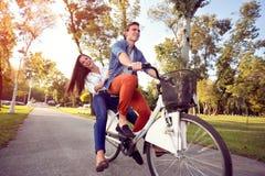 Équitation drôle heureuse de couples l'automne de bicyclette image libre de droits