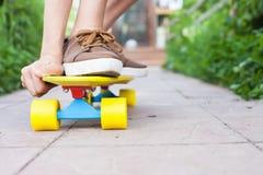Équitation en gros plan de planchiste par la planche à roulettes extérieure Skatebord à la ville, rue Photos stock