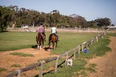 Équitation femelle d'amis au pré Photographie stock