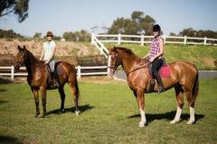 Équitation femelle d'amis pendant le jour ensoleillé Images stock