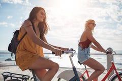 Équitation femelle de cycliste le long de la promenade Image stock