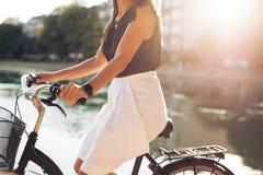 Équitation femelle sa bicyclette Photo stock