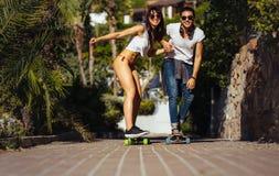 Équitation heureuse de couples sur des planches à roulettes des vacances Photographie stock libre de droits