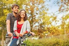 Équitation heureuse de couples sur un même vélo Photo libre de droits