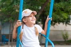 Équitation heureuse de fille sur une oscillation Image libre de droits