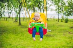 Équitation heureuse de petit garçon sur une oscillation en parc image libre de droits