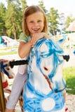 Équitation mignonne de petite fille sur un carrousel Photos stock