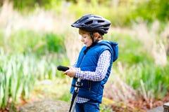 Équitation préscolaire mignonne de garçon d'enfant sur la bicyclette en parc Photographie stock