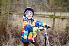 Équitation préscolaire mignonne de garçon d'enfant sur le scooter en parc Image stock