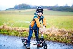 Équitation préscolaire mignonne de garçon d'enfant sur le scooter en parc Photographie stock libre de droits