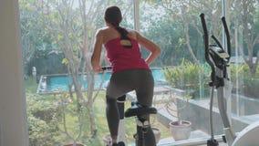 Équitation sportive de jeune femme sur le vélo d'exercice au gymnase dans le mouvement lent, vue arrière banque de vidéos