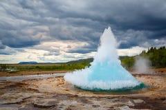 Éruption chaude de l'eau bleue de Strokkur de geyser célèbre de fontaine avec des clo Photos libres de droits