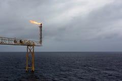 Éruption de torchage de pétrole marin et de gaz en mer pendant le backg de tempête Photos stock