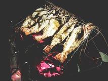 Ésta es gambas asadas a la parrilla en el carbón de leña bajo luz de una vela, t suave Imagen de archivo