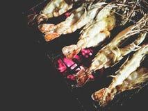 Ésta es gambas asadas a la parrilla en el carbón de leña bajo luz de una vela, t suave Imagenes de archivo