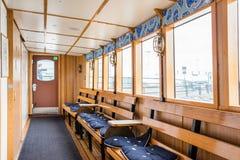ÉSTOCOLMO, SUÉCIA - 12 DE JULHO DE 2017: Interior do barco com janelas, os bancos de madeira e assentos macios Fotos de Stock Royalty Free