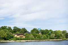 ÉSTOCOLMO, SUÉCIA - 6 DE JUNHO DE 2016: Casas litorais com bandeiras e os povos suecos do ciclismo, em uma ilha do arquipélago de Fotos de Stock Royalty Free