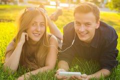 Été, amour et concept de personnes - fermez-vous des couples adolescents heureux se trouvant sur l'herbe avec des écouteurs et éc Photo stock