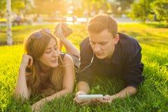 Été, amour et concept de personnes - fermez-vous des couples adolescents heureux se trouvant sur l'herbe avec des écouteurs et éc Image stock