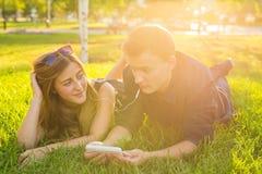 Été, amour et concept de personnes - fermez-vous des couples adolescents heureux se trouvant sur l'herbe avec des écouteurs et éc Image libre de droits