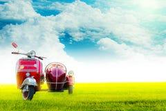 Été avec le Vespa, les voitures rouges et le ciel clair appropriés à écrire des messages photos libres de droits