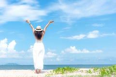 Été blanc de port de sourire de robe de mode de femme marchant sur la plage arénacée d'océan, beau fond de ciel bleu Enj heureux  images libres de droits