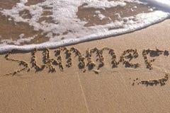 Été de Word écrit dans le sable de mer Les vagues ont enlevé l'inscription photos libres de droits