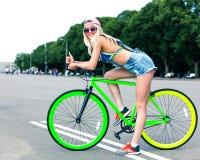 Été en parc de ville Belle fille blonde posant sur une bicyclette à la mode verte de difficulté dans un équipement frais Image stock
