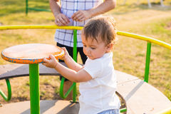 Été, enfance, loisirs et concept de la famille - enfant heureux et son père sur le cadre de s'élever de terrain de jeu d'enfants images stock