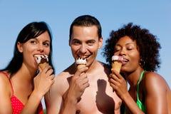 Été - homme et deux femmes mangeant la glace sur la plage Photos stock