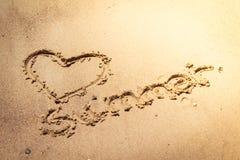 Été manuscrit dans le sable de la plage avec un beau coeur photos stock