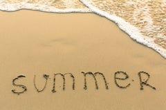Été - mot dessiné sur la plage de sable Image stock