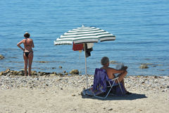 Été un ajouter à leur parapluie de plage au bord de la mer photographie stock libre de droits