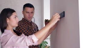 Étagère accrochante de ménages mariés sur le mur avec le ruban métrique dans des bras pendant les réparations dans le logement banque de vidéos