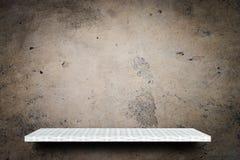 Étagère blanche vide sur le fond sale de ciment pour l'affichage de produit images libres de droits