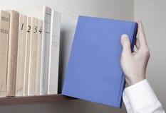 Étagère et livre bleu Images libres de droits