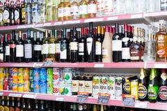 Étagères avec du vin, la vodka et les boissons non alcoolisées Photo libre de droits