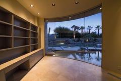 Étagères dans la chambre vide avec la vue d'étang par la fenêtre Photo libre de droits