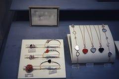 Étalage dans le magasin avec des bijoux de sur-vente : bracelets, chaînes, pendants, anneaux photos stock