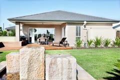 Étang d'eau en pierre fixe à la pelouse d'une maison moderne avec du bois Photos stock