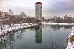 Étang de canard d'hiver en parc de ville avec des bâtiments reflétés dans l'eau photos stock