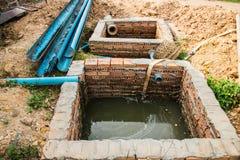 Étang de traitement des déchets et tuyau de PVC Photographie stock