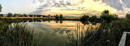 Étang du ` s de Josh dans Broomfield le Colorado au coucher du soleil se reflétant outre de l'eau, Rocky Mountains à l'arrière-pl Image stock