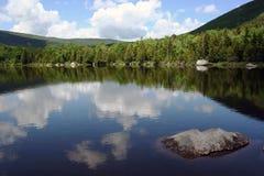 Étang scénique de montagne avec la réflexion du ciel Photographie stock libre de droits