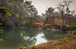 Étang scénique de village avec la natation de canards entourée avec des maisons de boue à un village indien Photos stock